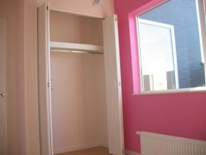 ピンクのアクセントクロスが映える洋室