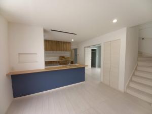 1Fリビング  キッチンの青いクロスが白を基調とした部屋でアクセントになり目を引きます